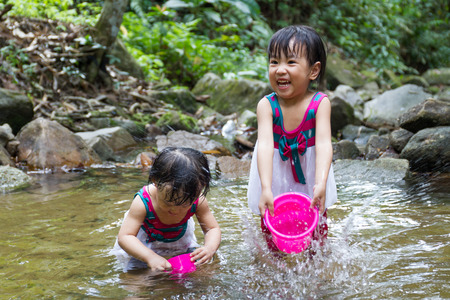 asia children: Asian Little Chinese Girls Playing in Creek in the Forest Stock Photo