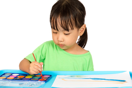 drawing table: Asian Little Chinese Girl Painting with Brush at Home Stock Photo