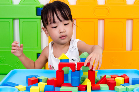 focus on: Asian Little Chinese Girl Playing Wooden Blocks at Home or Kindergarten Stock Photo