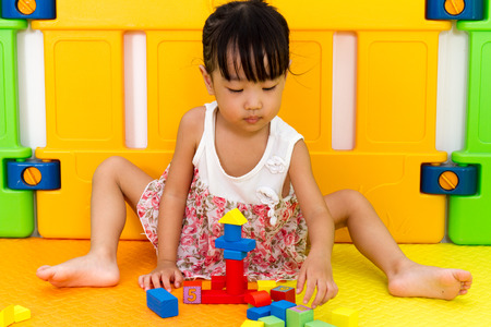 intelligent: Asian Little Chinese Girl Playing Wooden Blocks at Home or Kindergarten Stock Photo