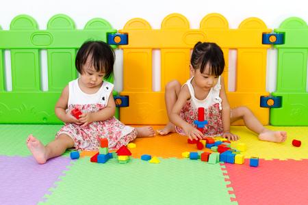 niñas chinas: Asian Little Chinese Girls Playing Wooden Blocks at Home or Kindergarten