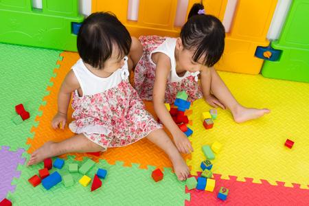 ni�as chinas: Asi�ticos ni�as chinas que juega bloques de madera en el hogar o jard�n de infancia