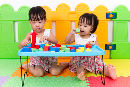 ni�as chinas: Asian Little Chinese Girls Playing Wooden Blocks at Home or Kindergarten