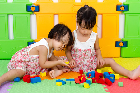 Asian Little Chinese Girls Playing Wooden Blocks at Home or Kindergarten