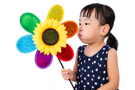 windmill: Asian Little Chinese Girl Blowing Colorful Windmill isolated on White Background