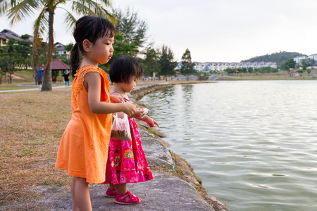 ni�as chinas: Asian Little Chinese Girls Feeding Fish in the Park