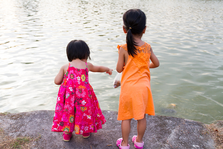 niñas chinas: Asiáticos niñas chinas alimentación de los peces en el Parque