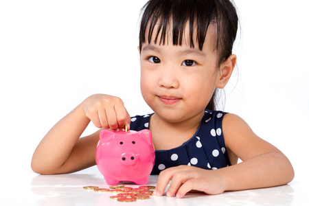 asian coins: Asian Little Chinese Girl Putting Coins into Piggy Bank isolated on White Background
