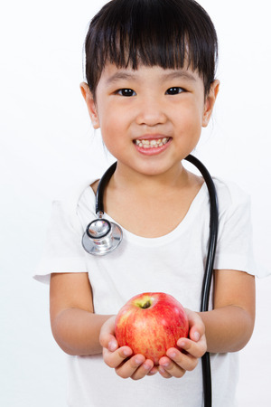 asian children: Asian Little Chinese Girl Dressed up as Doctor with a Stethoscope Holding an apple isolated on white background