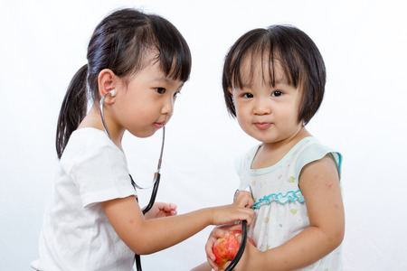 Hospital care: Asian Little Chinese Girls Playing as Doctor and Patient with Stethoscope isolated on white background