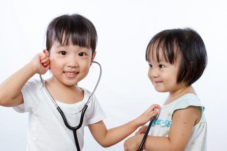 niñas chinas: Asiáticos niñas chinas que juegan como Médico y paciente con el estetoscopio aislado en el fondo blanco Foto de archivo