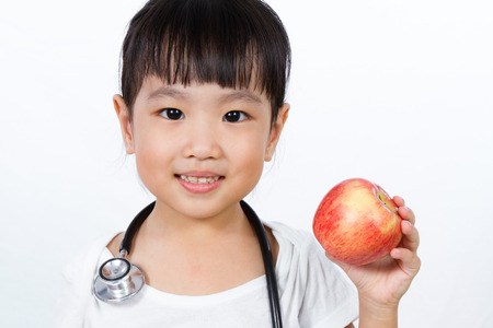 physician: Asian Little Chinese Girl Dressed up as Doctor with a Stethoscope Holding an apple isolated on white background