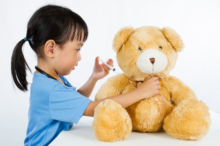 baby playing: Asian Little Chinese Girl Playing Doctor with Teddy Bear isolated on white background Stock Photo