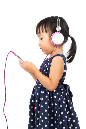 mobile headset: Asian Little Chinese Girl Using Mobile Phone with Headset isolated on White Background Stock Photo