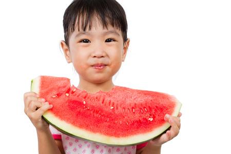 niña comiendo: Pequeña muchacha asiática china que come la sandía aislada en el fondo blanco Foto de archivo