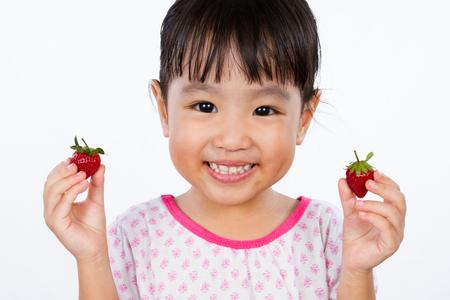 niños comiendo: Pequeña muchacha asiática china que sostiene la fresa aislado en el fondo blanco