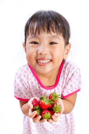 comiendo frutas: Pequeña muchacha asiática china que sostiene la fresa aislado en el fondo blanco