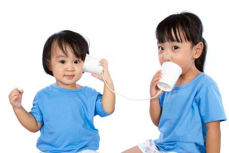 niñas chinas: Asiáticos niñas chinas jugar con las tazas de papel aislado en el fondo blanco