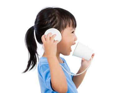 comunicarse: Poco asiático niña china jugar con las tazas de papel aislado en el fondo blanco
