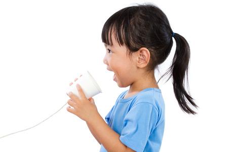 comunicarse: Poco Muchacha china asiática que juega con la taza de papel aislado en el fondo blanco Foto de archivo