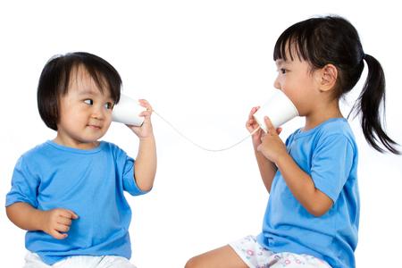 comunicarse: Asiáticos niñas chinas jugar con las tazas de papel aislado en el fondo blanco