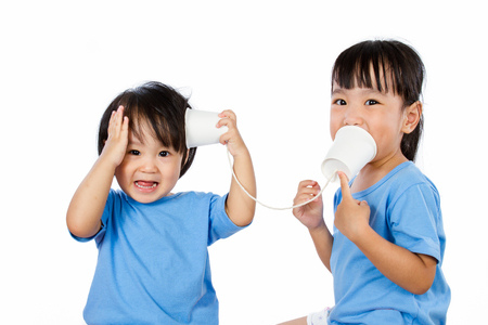 communicating: Asian Little Chinese Girls Playing with Paper Cups isolated on White Background Stock Photo