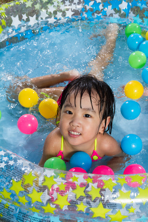 kiddie: Asian Little Chinese Girl Playing in an Inflatable Rubber Swimming Pool Outdoors