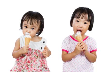 niñas chinas: Asiáticos niñas chinas comiendo helado aislado sobre fondo blanco Foto de archivo