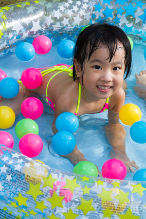 asia children: Asian Little Chinese Girl Playing in an Inflatable Rubber Swimming Pool Outdoors