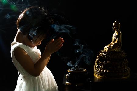 incienso: Poco Muchacha china asiática que ruega delante de Buda en aislados Fondo Negro