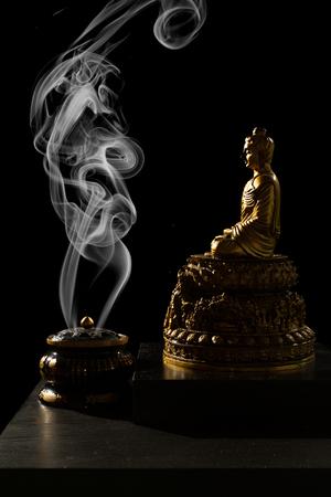 budda: Sitting Bronze Budda with Incense Burner in isolated Black Background Stock Photo