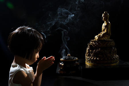 rites: Asian Little Chinese Girl Praying in front of Buddha in isolated Black Background