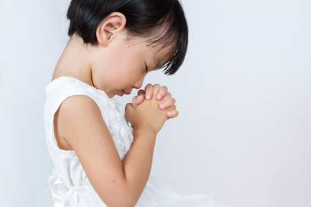 Asian Little Chinese Girl Praying in isolated White Background Stock Photo