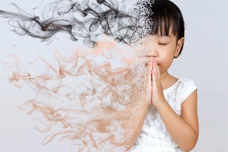 アジア小さな中国の少女祈って分離ホワイト バック グラウンドで