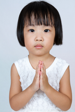 plead: Asian Little Chinese Girl Praying in isolated White Background Stock Photo