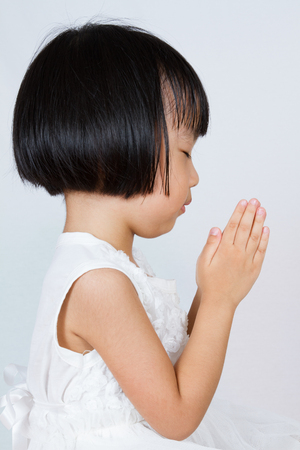 kids hand: Asian Little Chinese Girl Praying in isolated White Background Stock Photo