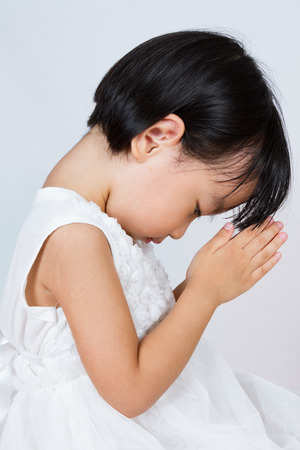bless: Asian Little Chinese Girl Praying in isolated White Background Stock Photo