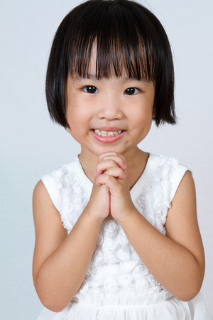 implore: Asian Little Chinese Girl Praying in isolated White Background Stock Photo