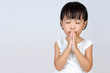 Bambina asiatica cinese Pregare in isolato sfondo bianco Archivio Fotografico