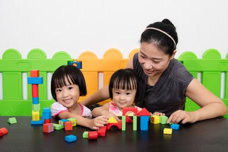 アジアの子供たちとお母さんの遊び場で一緒に遊んで