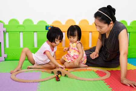 family activities: Asian Kids and Mother Playing Together at Playground