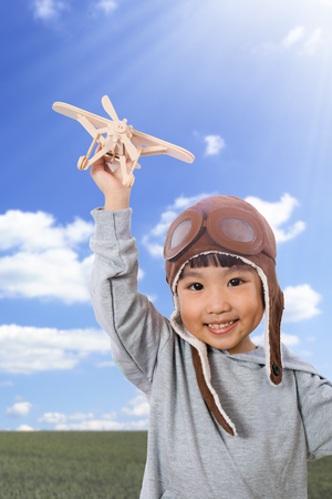 fantasize: Asian Little Chinese Girl Playing with Toy Airplane against Blue Sky Background