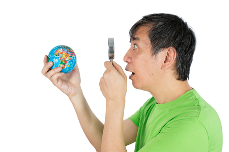 optical people person planet: Asian Chinese Man Looking At Globe Through Magnifying Glass in isolated White Background