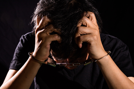 swindler: Asian Chinese Man with handcuffs in isolated Black Background Stock Photo