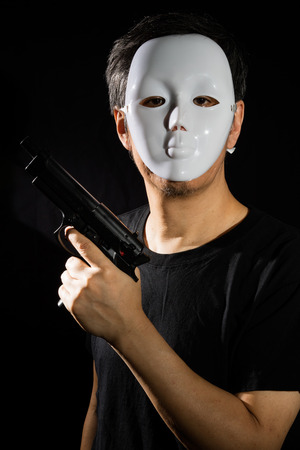 guise: Man in a Mask with a Gun in isolated Black Background Stock Photo