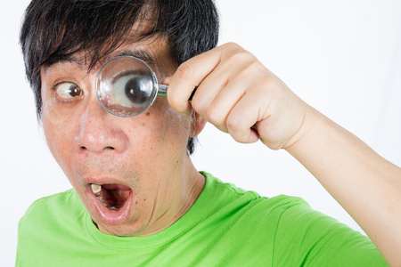amplify: Asian Chinese Man Looking through a Magnifying Glass in isolated White Background Stock Photo