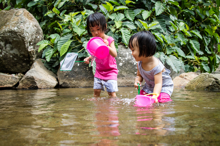 ni�as chinas: Asi�ticos ni�as chinas que juegan en Cala en el bosque Foto de archivo