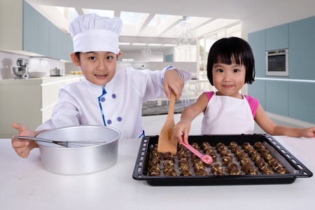 playing with spoon: Asian Chinese Kid Baking Cookies against Kitchen Background Stock Photo