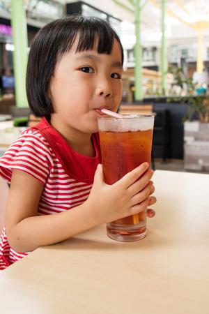 ice tea: Asian Little Chinese Girl Drinking Ice Tea in Outdoor Cafe