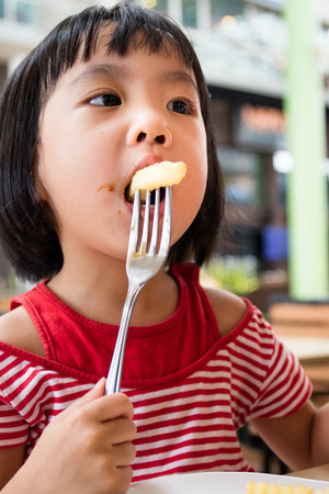 messy kids: Asian Little Chinese Girl Eating French Fries in Outdoor Cafe Stock Photo